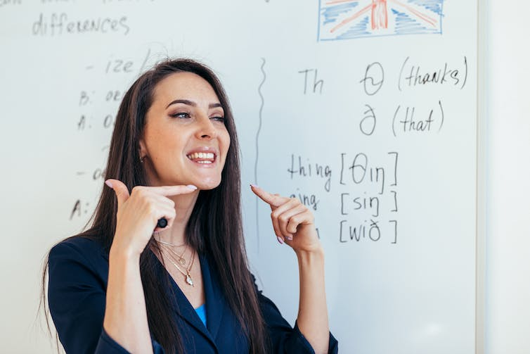 A woman standing in front of a whiteboard shows how to pronounce different sounds