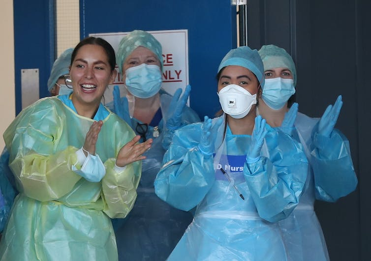 Four women in personal protective equipment clap at a hospital door.
