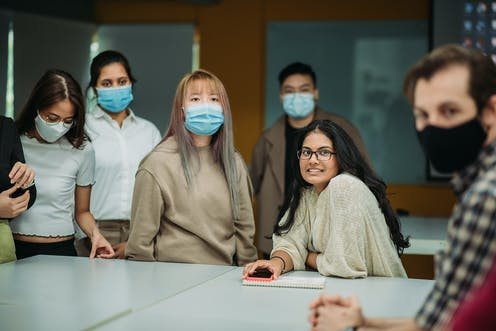A group of Asian American students mostly wearing masks sit in class.