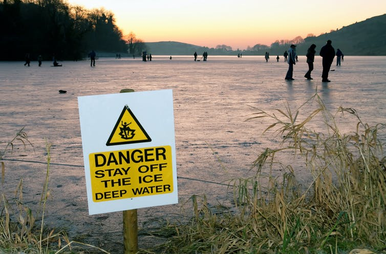 people walking on a frozen lake with a danger 'thin ice' sign in the foreground