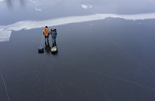 two men pulling sleds across a frozen lake after fishing