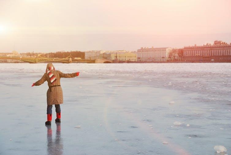 A woman balances on a frozen river