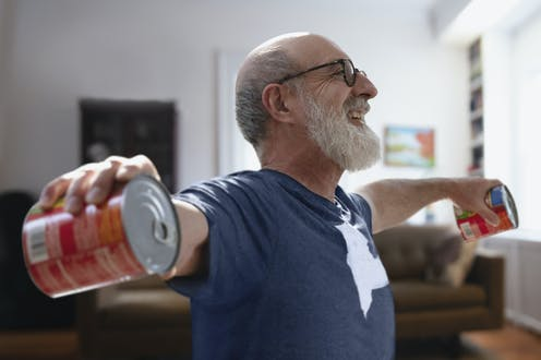 Older man excercising from home by lifting two cans of tomatoes up to shoulder height.