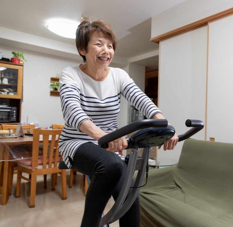 An older woman pedaling on an exercise bicycle in her living/dining room.