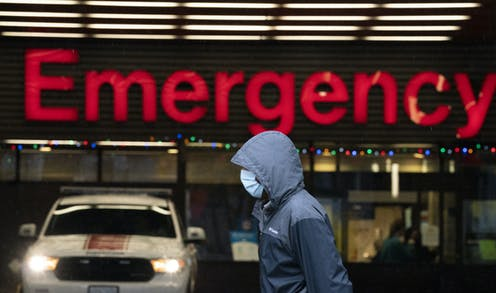 A person wearing a mask walks past a large red emergency sign.