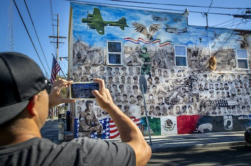Man uses cell phone to photograph a mural with Mexican and American flags