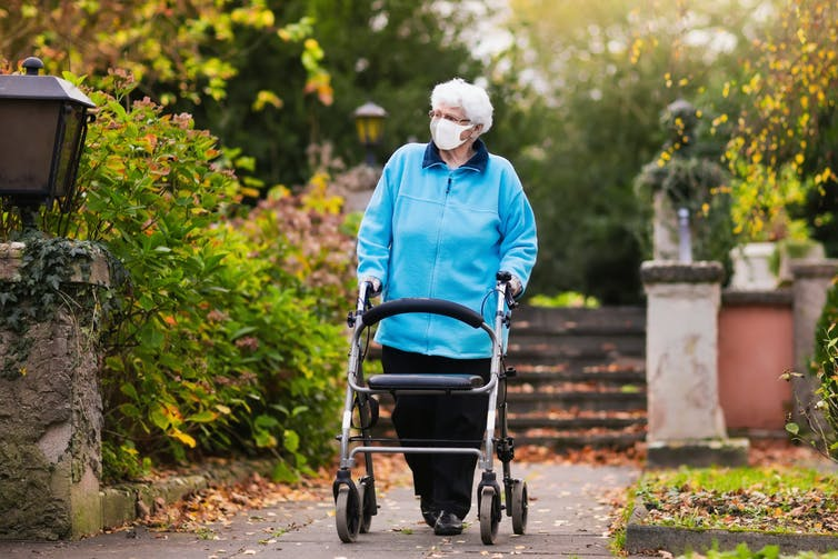 An elderly lady wearing a mask walks with a frame in a garden.