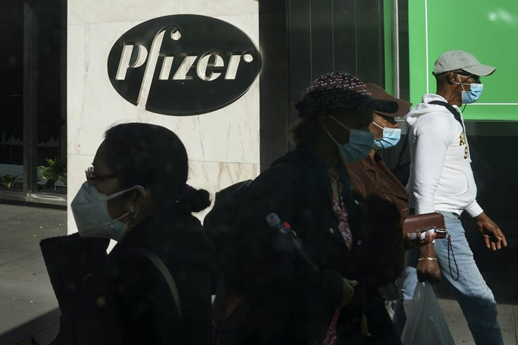 People walking past a 'Pfizer' sign at Pfizer world headquarters in New York.