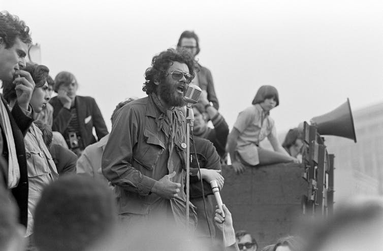 Archival photo of man in front of microphone with small crowd behind him