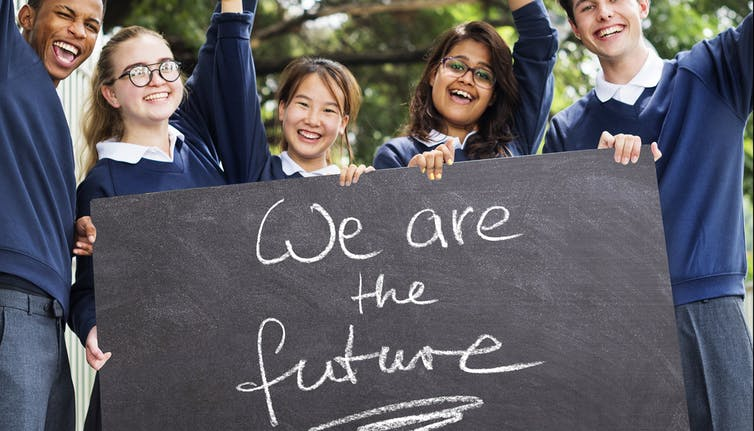 Children in uniform hold sign with caption, 'We are the future'