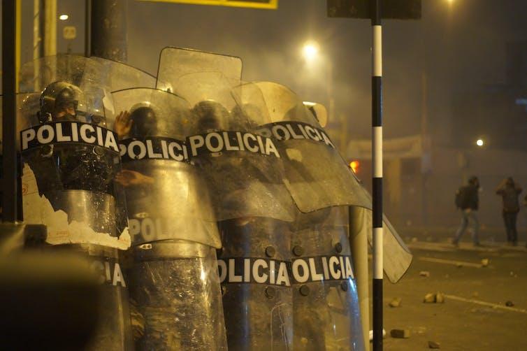 Los policías se cubren con sus escudos durante un enfrentamiento con manifestantes durante la protesta contra la decisión del Congreso de destituir al expresidente Martín Vizcarra. Lima, 12 de noviembre de 2020-Shutterstock / Joseph Everth