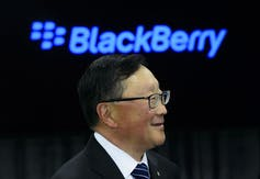 John Chen smiles with a blue Blackberry logo in the background.