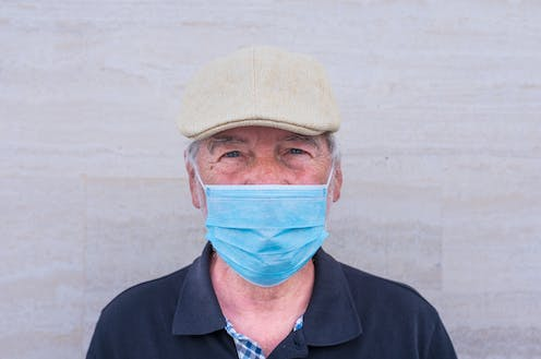 Older man wearing a mask.