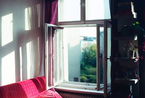 An open window next to a red couch.