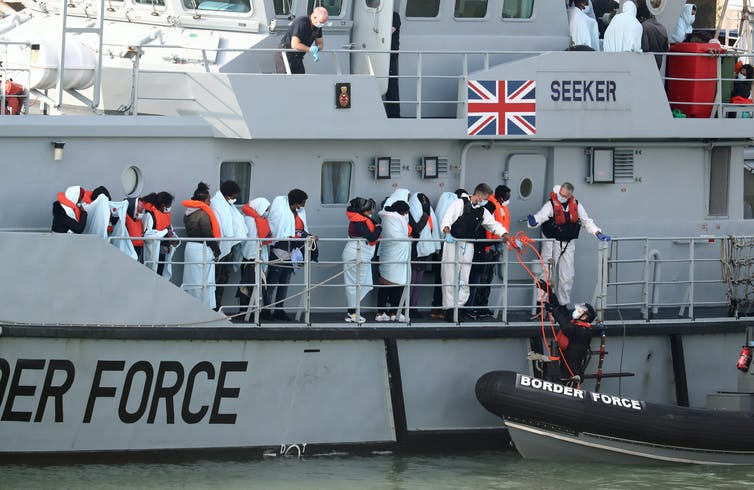 People with life jackets on waiting on a Border Force boat.