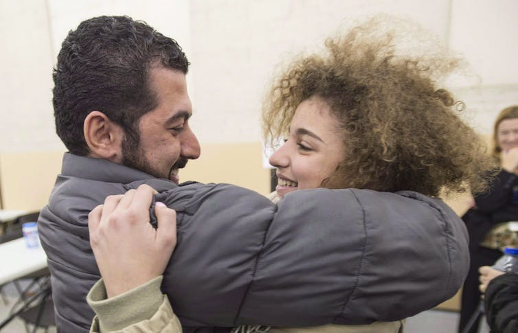 A teenaged girl with curly hair embraces a man.