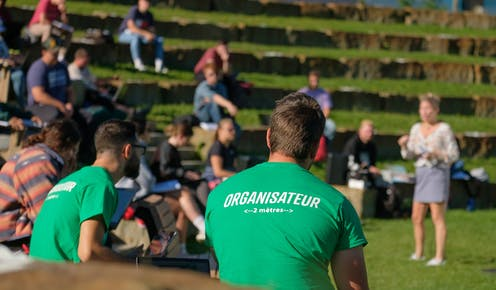 The back of  a young man in a t-shirt in an outdoor ampitheatre.