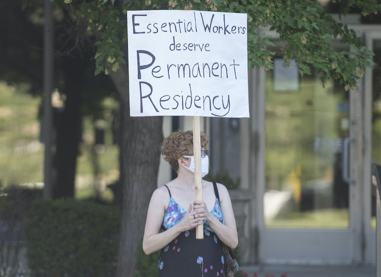 A woman carries a sign that reads: Essential workers deserve permanent residency.