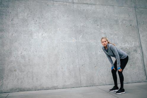 Mujer con ropa deportiva descansando tras hacer esfuerzo físico.