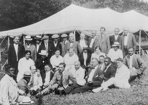 A group of people gather outdoors, in front of a tent, in an old photo.
