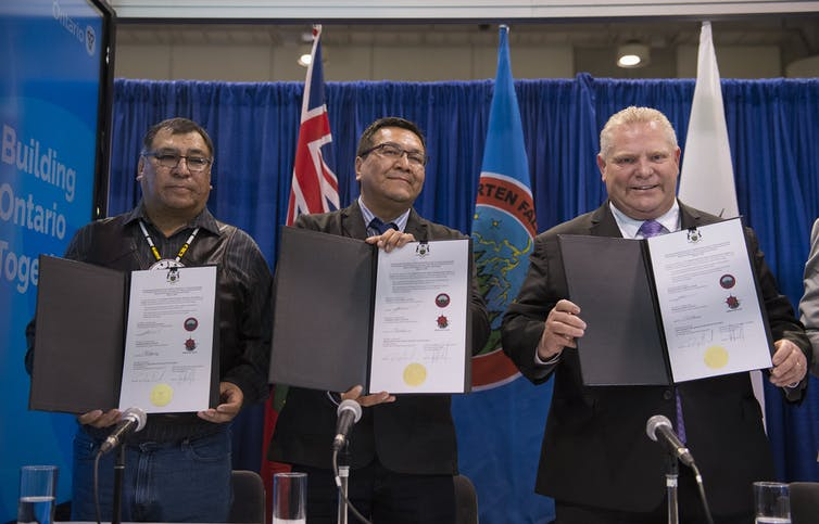 Ontario Premier Doug Ford, right, Chief Cornelius Wabasse, Webequie First Nation, left, and Chief Bruce Achneepineskum, Marten Falls First Nation, centre, show off their signed agreement