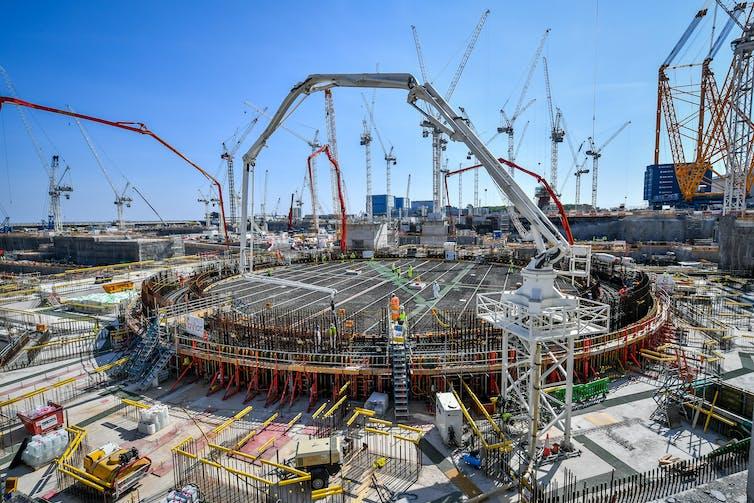 Lots of cranes surround a construction site.