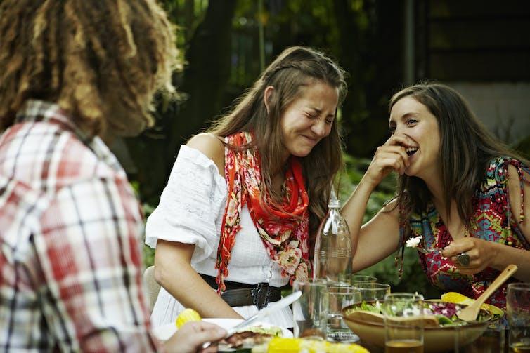 Des femmes riant ensemble lors d'un repas en plein air.