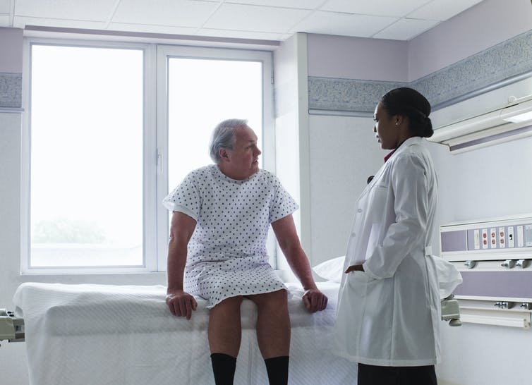 A black woman doctor speaking with an older white man.