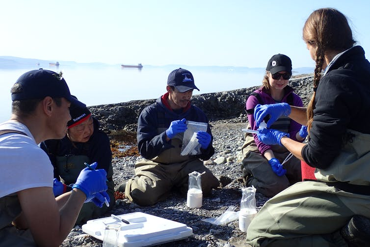 A group of people sit on shore learning to use sampling equipment.