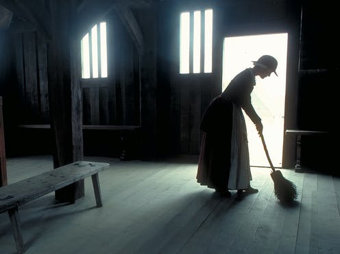 A historical re-enactor sweeps an empty house at Plymouth Plantation.