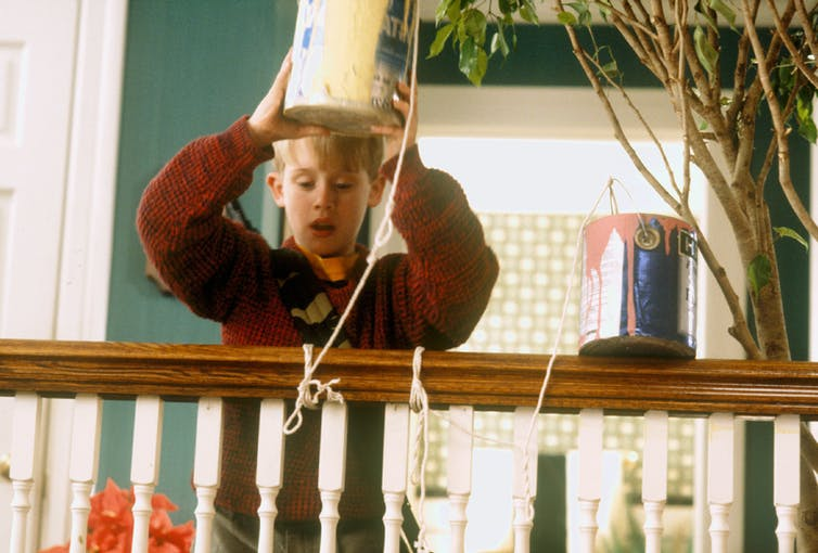 Kevin holds paint cans over the banister.