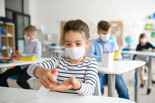 Girl wearing mask in class, and putting on hand sanitiser.