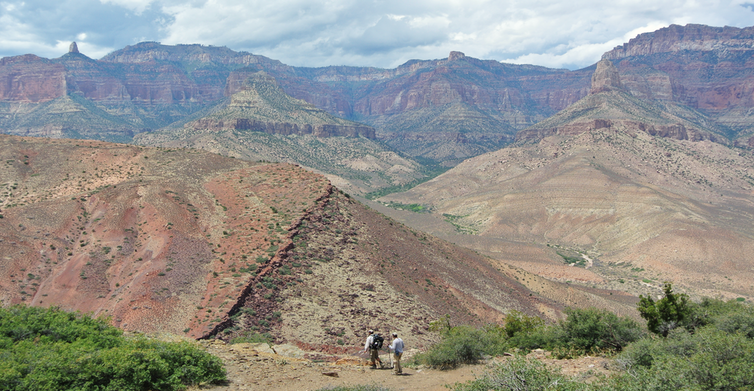 Photo showing two small figures in the foreground in front of large rocky landscape in the Grand Canyon.