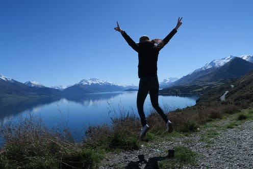 woman jumping near lake