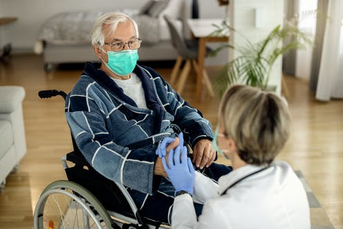 persona mayor con mascarilla en silla de ruedas le da la mano a cuidadora con mascarilla y guantes.