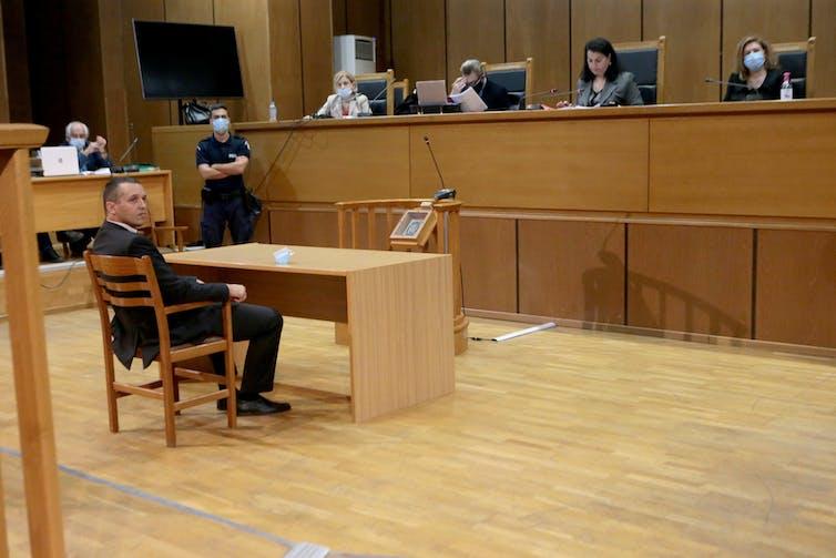 Ilias Kasidiaris, ancien membre de Golden Dawn, siégeant au tribunal devant une rangée de juges.