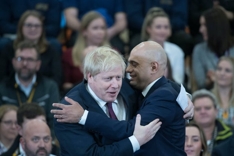 Boris Johnson and Sajid Javid embracing in front of seated audience.