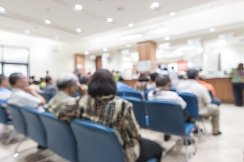 A blurred image of patients in a waiting room.