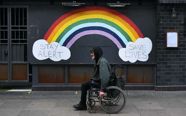 """A man in a wheelchair passes a street mural of a rainbow and the slogan """"stay alert save lives""""."""