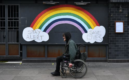 "A man in a wheelchair passes a street mural of a rainbow and the slogan ""stay alert save lives""."
