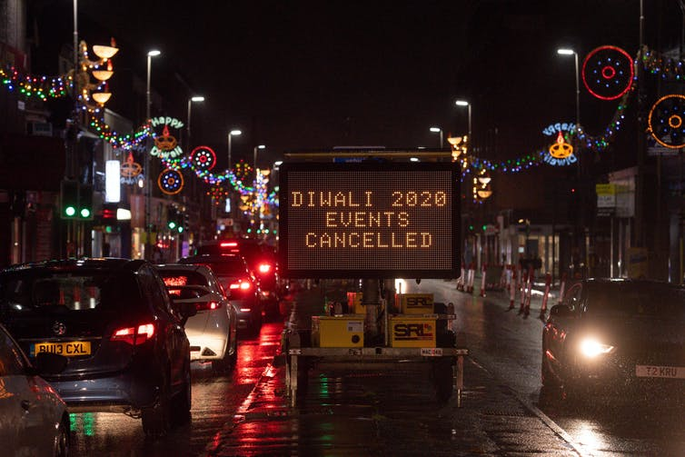 A sign on a nighttime highstreet saying 'Diwali 2020 Events Cancelled'