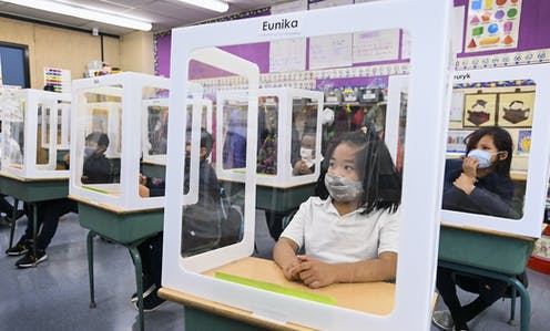 Children wearing masks behind screens in a classroom.