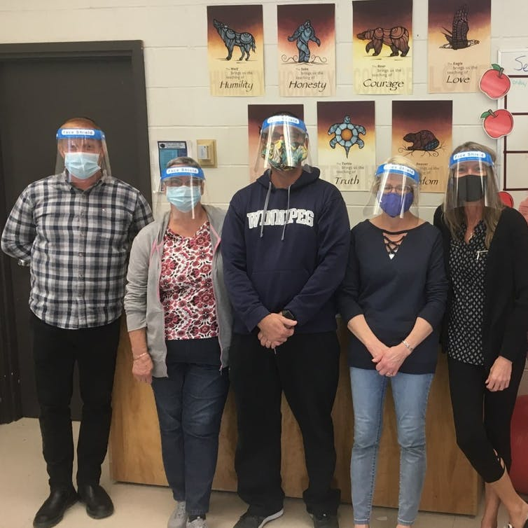 Educational assistants standing wearing face shields.