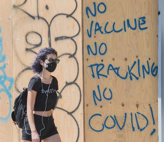 A woman wearing a face mask walks by a board-up window with 'no vaccine no tracking no COVID!' written on it in blue letters.