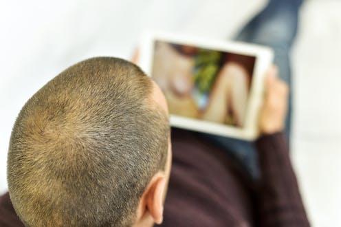 Hombre con el pelo rapado viendo a una mujer desnuda en una pantalla.