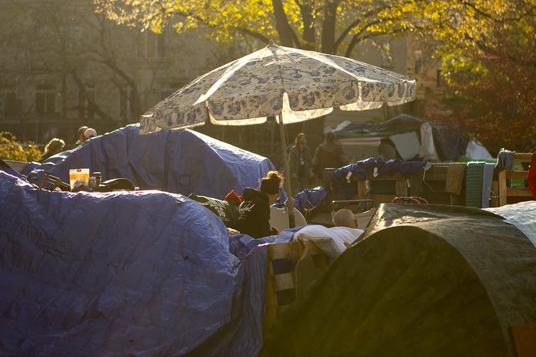 A woman is seen near a large sun umbrella in a Toronto homeless encampment.