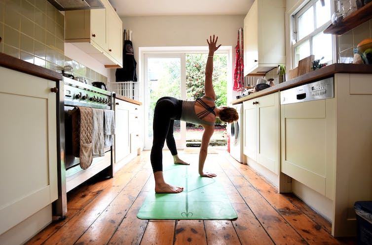 Woman doing yoga in her kitchen