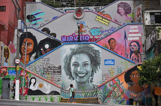 Mural featuring Black women, with a few people walking in front of it