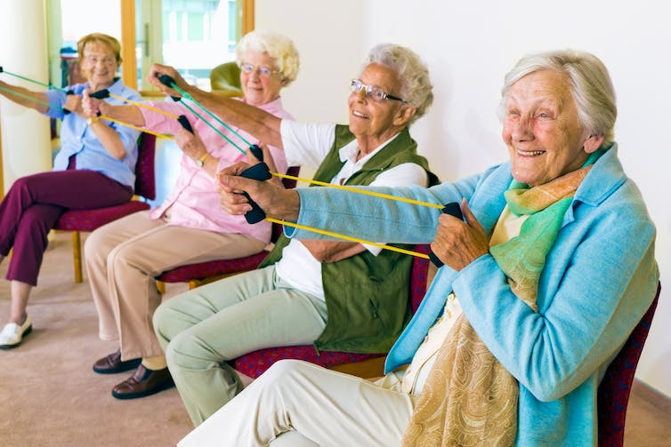 Aged care residents smiling as they exercise