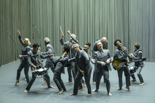 David Byrne with musicians dance on stage.